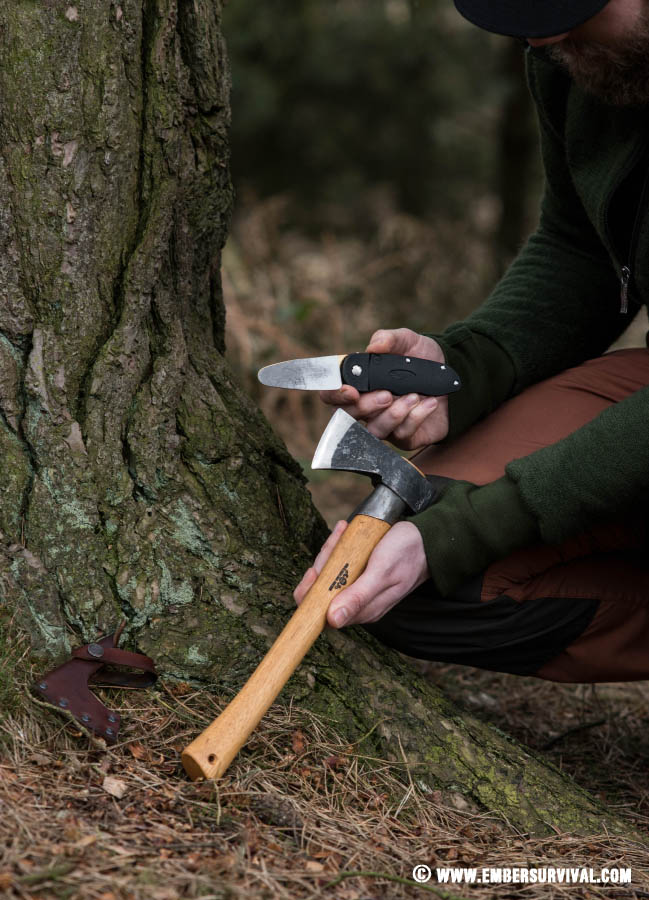 Woodsman in forest sharpening axe